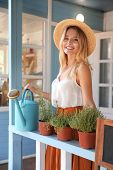 Young Woman With Watering Can And Home Plants On Veranda poster