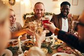 Multi-ethnic Group Of Cheerful Adult People Clinking Champagne Glasses While Enjoying Christmas Dinn poster