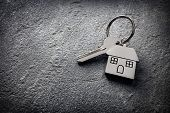House key on a house shaped keychain on stone concept for real estate, moving home or renting proper poster