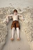 Boy  Is Lying In A Sandy Bed At The Beauti Ful Beach