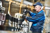 picture of assemblage  - adult experienced industrial worker during heavy industry machinery assembling on production line manufacturing workshop - JPG
