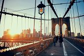 Walk on Brooklyn Bridge with pedestrians at sunset in downtown Manhattan New York City poster