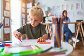 Young caucasian child playing at playschool with teacher. Mother and son at playroom drawing a draw  poster