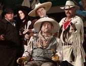 stock photo of antique wheelchair  - Injured senior cowboy and friends with guns drawn - JPG