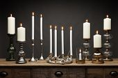 A Group Of Candle Sticks And Candle Holders And Glowing Candles, Shot On A Wooden Table, With A Dark poster