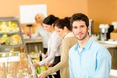 Business man take cafeteria lunch food from display cabinet self-service