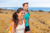 Happy hikers hiking on trail hike in beach Hawaii Travel. Young smiling people walking on nature out poster