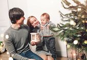 Christmas Family With Baby Smiling Near The Xmas Tree. Living Room Decorated By Christmas Tree And P poster