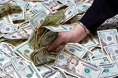 picture of american money  - Womans hand grabbing money from a huge pile of dollars - JPG