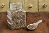 chia seeds in glass jar and on measuring aluminum tablespoon with a vintage drawer cabinet in backgr