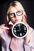 stock photo of dork  - Concerned Business Woman In Dork Glasses Pointing To Delayed Black Office Clock In A Depiction Of Tardy Time Management - JPG
