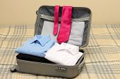 stock photo of carry-on luggage  - Open grey suitcase with clothing on bed - JPG