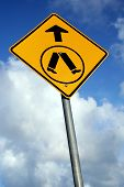 stock photo of pedestrian crossing  - a yellow pedestrian crossing sign against a blue cloudy sky - JPG