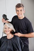 Portrait of male hairstylist with dryer setting up senior woman's hair in beauty parlor