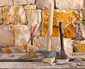 Hammer mason tools of stonecutter masonry work in a construction stone wall