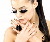 image of minx  - Closeup portrait of the beautiful woman with long black false eyelashes makeup and golden nails - JPG