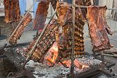stock photo of brazier  - An asado is a roasted meat of beef or various other meats which are cooked on a typical barbecue with vertical grills placed around at fire and embers in a big brazier - JPG