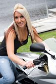 stock photo of crotch-rocket  - A young blonde woman poses on her motorcycle - JPG