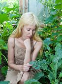 The young attractive woman is upset - caterpillars eat leaves of plants