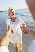 Happy senior man and woman couple dancing and holding hands on a deserted tropical beach with bright