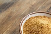small ceramic bowl of unrefined coconut palm sugar against an out of focus wood background - copy sp