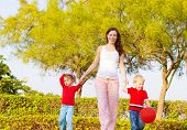 Picture of happy young family in park, cute pregnant mother with two sweet child walking outdoors in