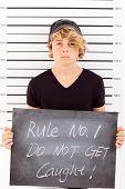 teen boy holding a blackboard criminal mug shot