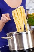 Female Hands Raising Cooked Pasta Out Of The Pot