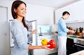 healthy eating couple get fresh vegetables out of the fridge to cook food