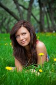 beautiful brunette girl lying on the grass
