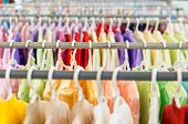 foto of apparel  - Rows of new colorful clothing on hangers at shop in foreground and background. Great choice of casual clothes of different colors. Apparel ready for sale. Going shopping. Trade and commerce.