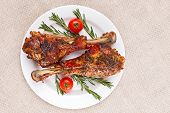 Roasted turkey legs on white plate with cherry tomato and rosemary