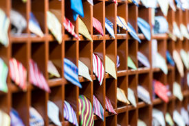 stock photo of going out business sale  - Rows of new colorful ties on shelves at shop. Great section of ties in different colors. Big choice of apparel or business style accessories ready for sale. Going shopping. Trade and commerce. ** Note: Shallow depth of field - JPG