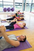 Sporty people doing the supine wind release posture at yoga class in fitness studio