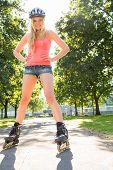 Casual cheerful blonde standing hands on hips wearing inline skates in a park