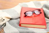 Composition with old book, eye glasses and plaid on wooden background