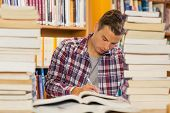 Focused handsome student studying between piles of books in library