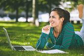 Laughing casual student lying on grass taking notes on campus at college