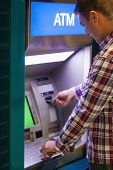 Brunette student withdrawing cash at an ATM