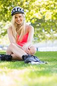 Casual cheerful blonde wearing inline skates and helmet sitting in a park