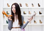 Woman keeps two high heeled shoes in the shopping mall and can't choose the one for her