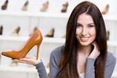 Portrait of woman keeping brown leather shoe in shopping center