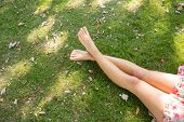 Close up of female crossed legs lying on the grass in a park on a sunny day