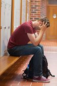 Upset handsome student holding his head in school