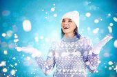 Joyful girl in winterwear enjoying snowfall