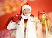Portrait of happy girl in winterwear holding paper bags and looking at camera