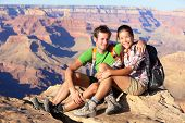 Hiking couple portrait - hikers in Grand Canyon enjoying view of nature landscape looking at camera smiling happy. Young couple trekking, relaxing after hike on south rim of Grand Canyon, Arizona, USA