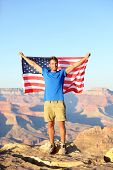 American USA flag - tourist in Grand Canyon. Happy young man hiking and cheering at Grand Canyon sou