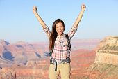 Happy winner hiker in Grand Canyon cheering with arms raised up in winning gesture enjoying the beautiful landscape. Hiking girl wearing backpack during summer in Grand Canyon, Arizona, United States.