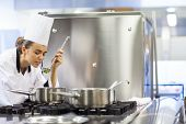 Young pretty chef tasting sauce in professional kitchen